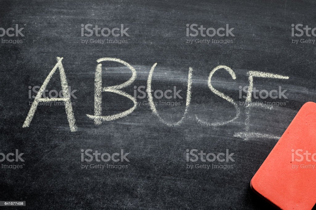 erasing abuse, hand written word on blackboard being erased concept stock photo