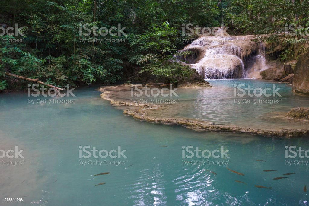 Erawan Waterfalls with clear green pond and fish stock photo