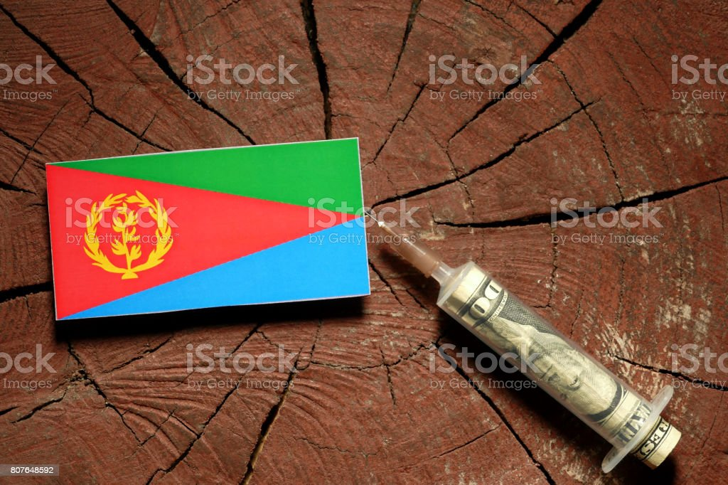 Eritrean flag on a stump with syringe injecting money in flag stock photo