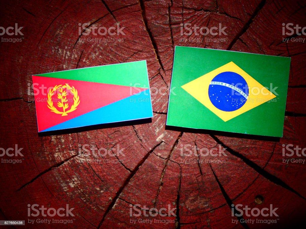Eritrean flag with Brazilian flag on a tree stump isolated stock photo