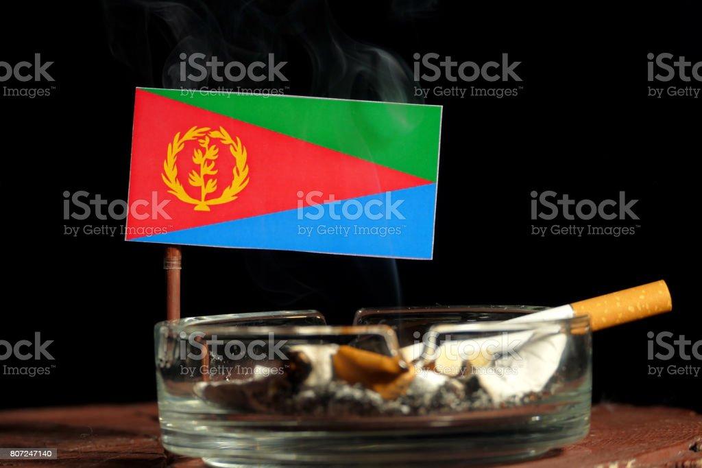 Eritrean flag with burning cigarette in ashtray isolated on black background stock photo