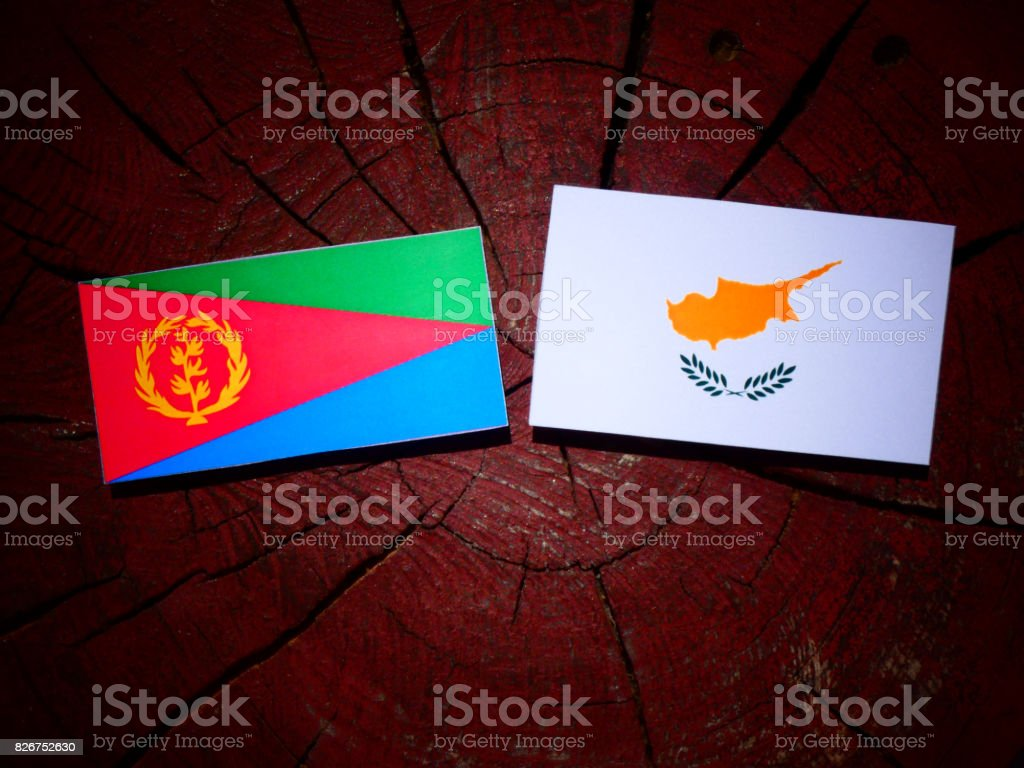 Eritrean flag with Cypriot flag on a tree stump isolated stock photo