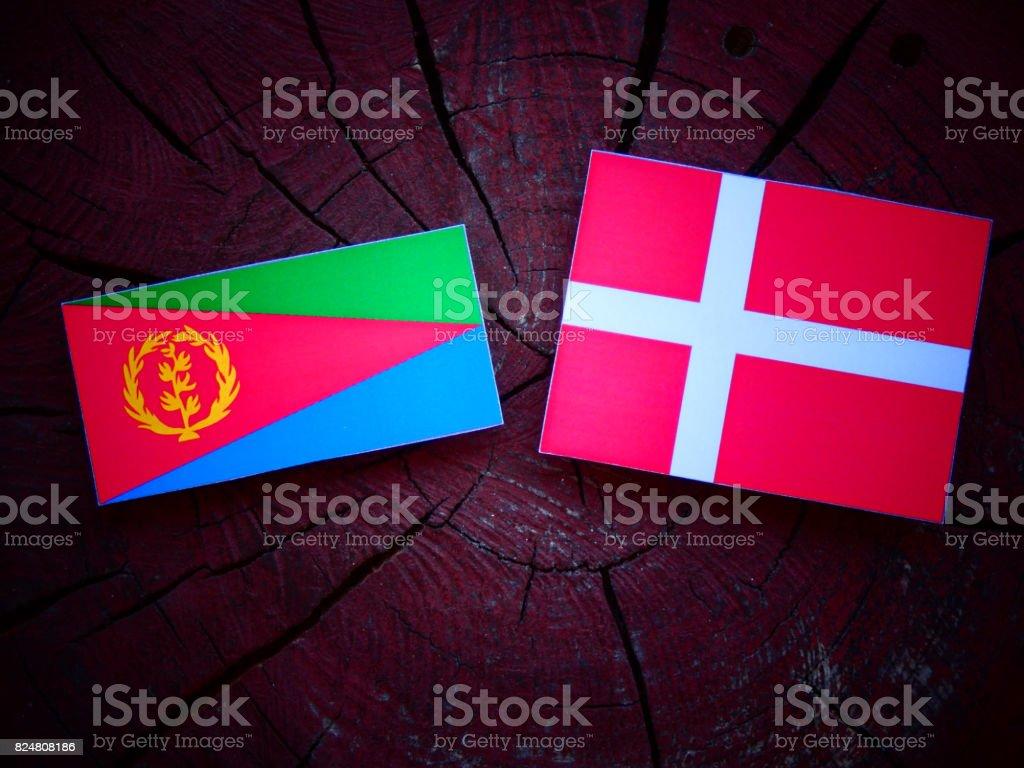 Eritrean flag with Danish flag on a tree stump isolated stock photo