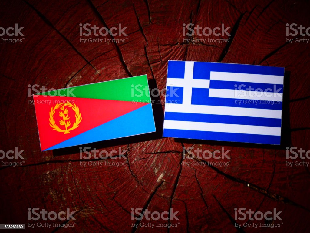 Eritrean flag with Greek flag on a tree stump isolated stock photo