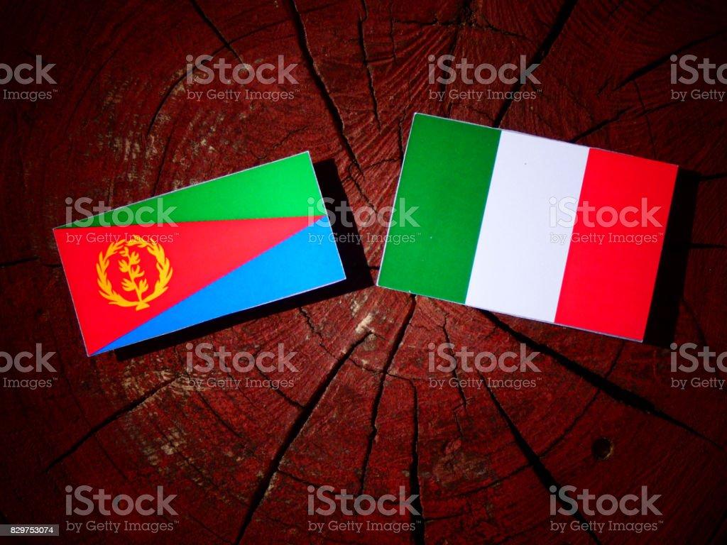 Eritrean flag with Italian flag on a tree stump isolated stock photo