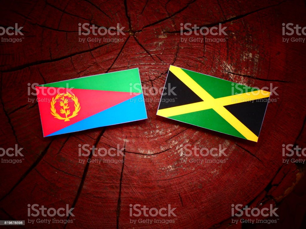 Eritrean flag with Jamaican flag on a tree stump isolated stock photo
