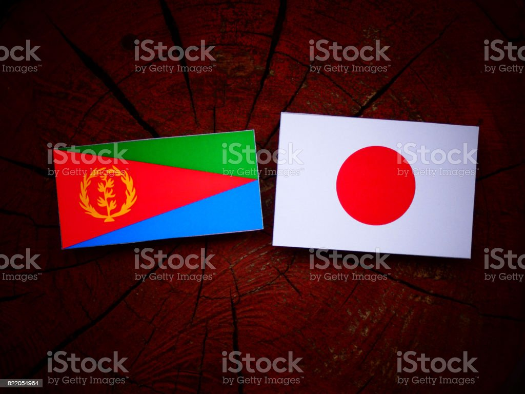 Eritrean flag with Japanese flag on a tree stump isolated stock photo