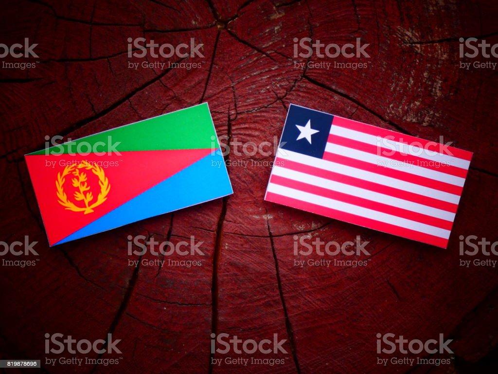 Eritrean flag with Liberian flag on a tree stump isolated stock photo