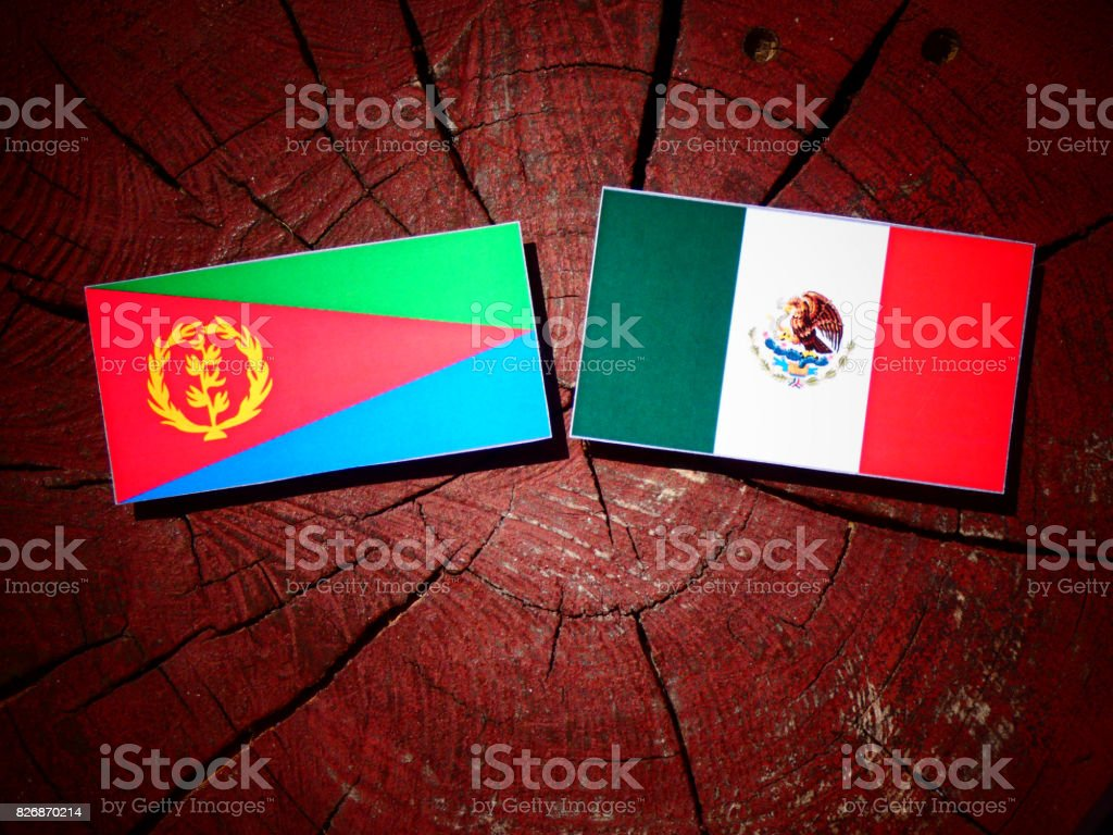 Eritrean flag with Mexican flag on a tree stump isolated stock photo