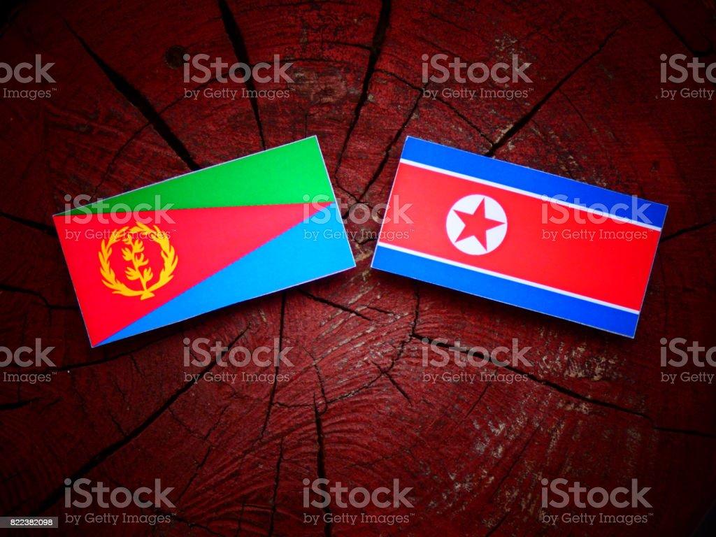 Eritrean flag with North Korean flag on a tree stump isolated stock photo