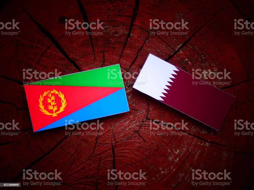 Eritrean flag with Qatari flag on a tree stump isolated stock photo
