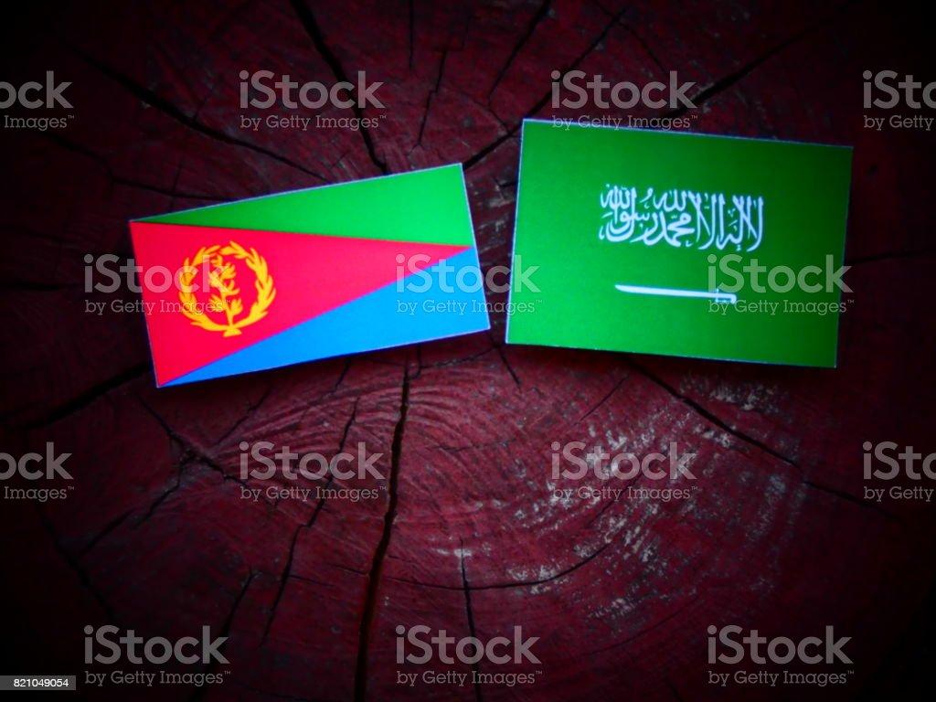 Eritrean flag with Saudi Arabian flag on a tree stump isolated stock photo