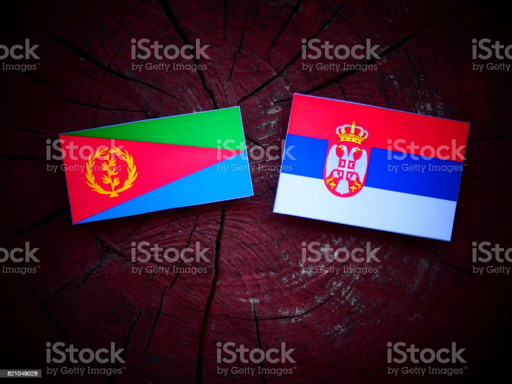 Eritrean flag with Serbian flag on a tree stump isolated stock photo