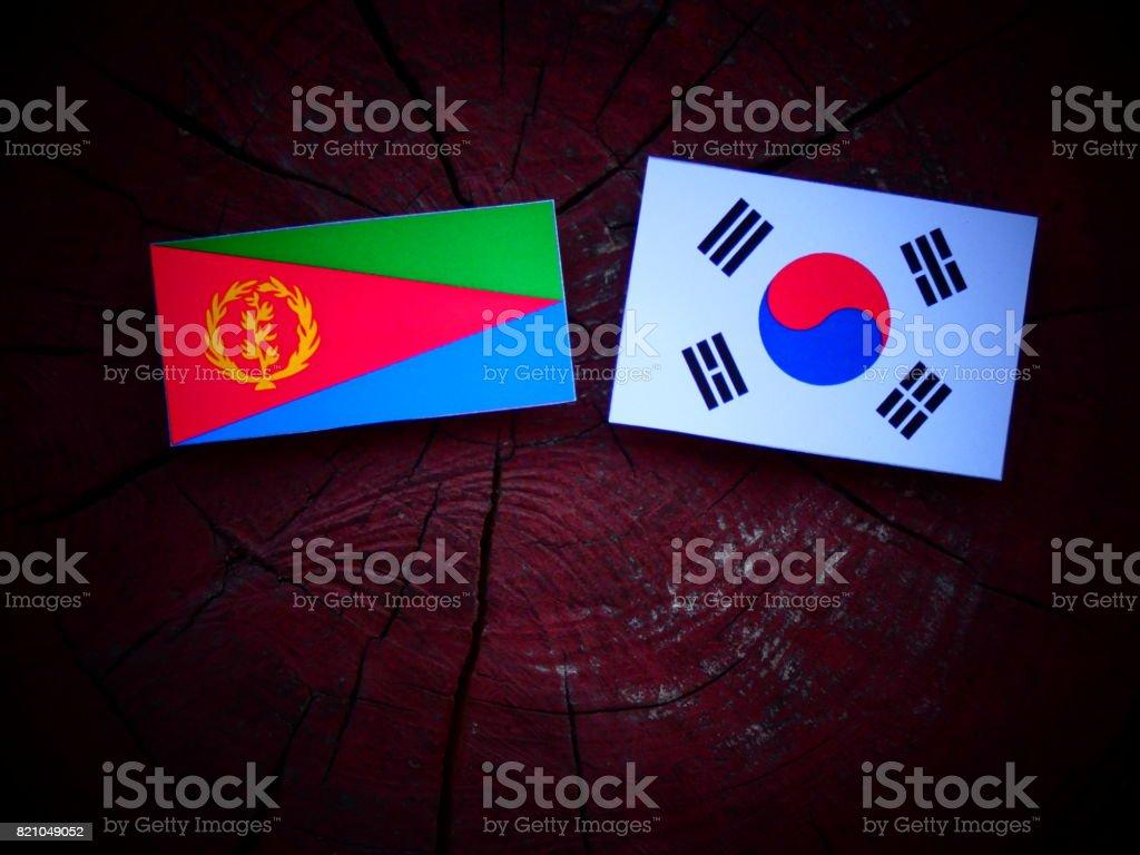 Eritrean flag with South Korean flag on a tree stump isolated stock photo