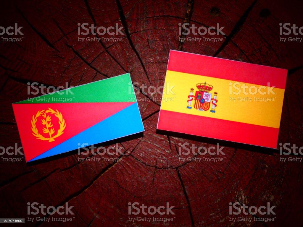 Eritrean flag with Spanish flag on a tree stump isolated stock photo