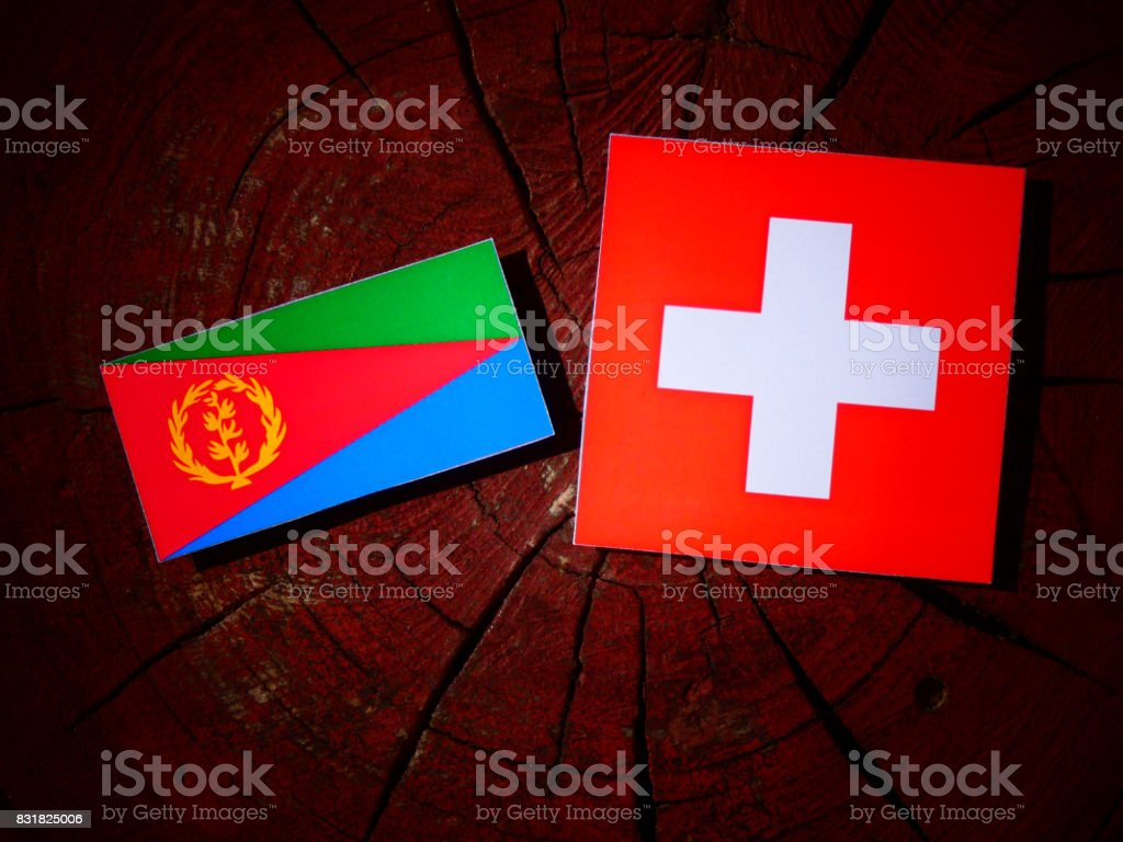 Eritrean flag with Swiss flag on a tree stump isolated stock photo