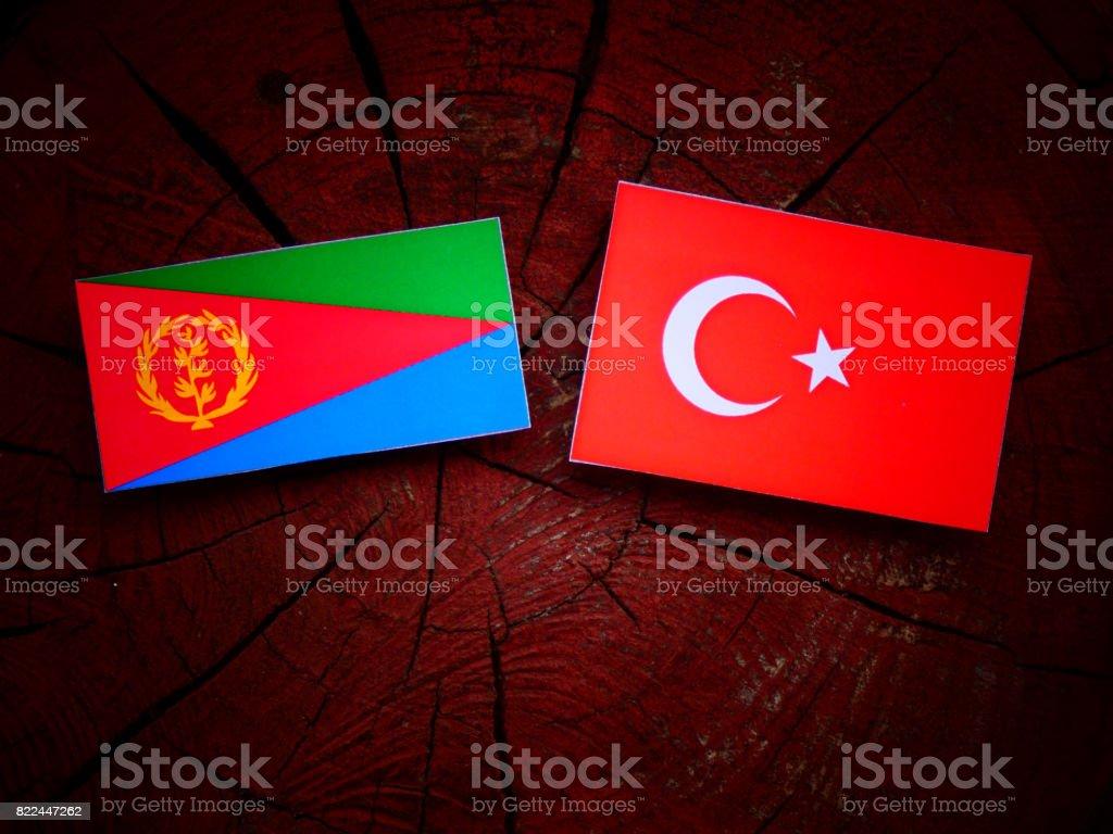 Eritrean flag with Turkish flag on a tree stump isolated stock photo