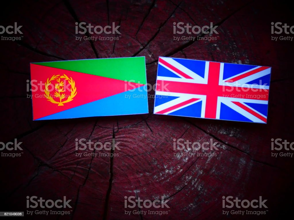 Eritrean flag with UK flag on a tree stump isolated stock photo