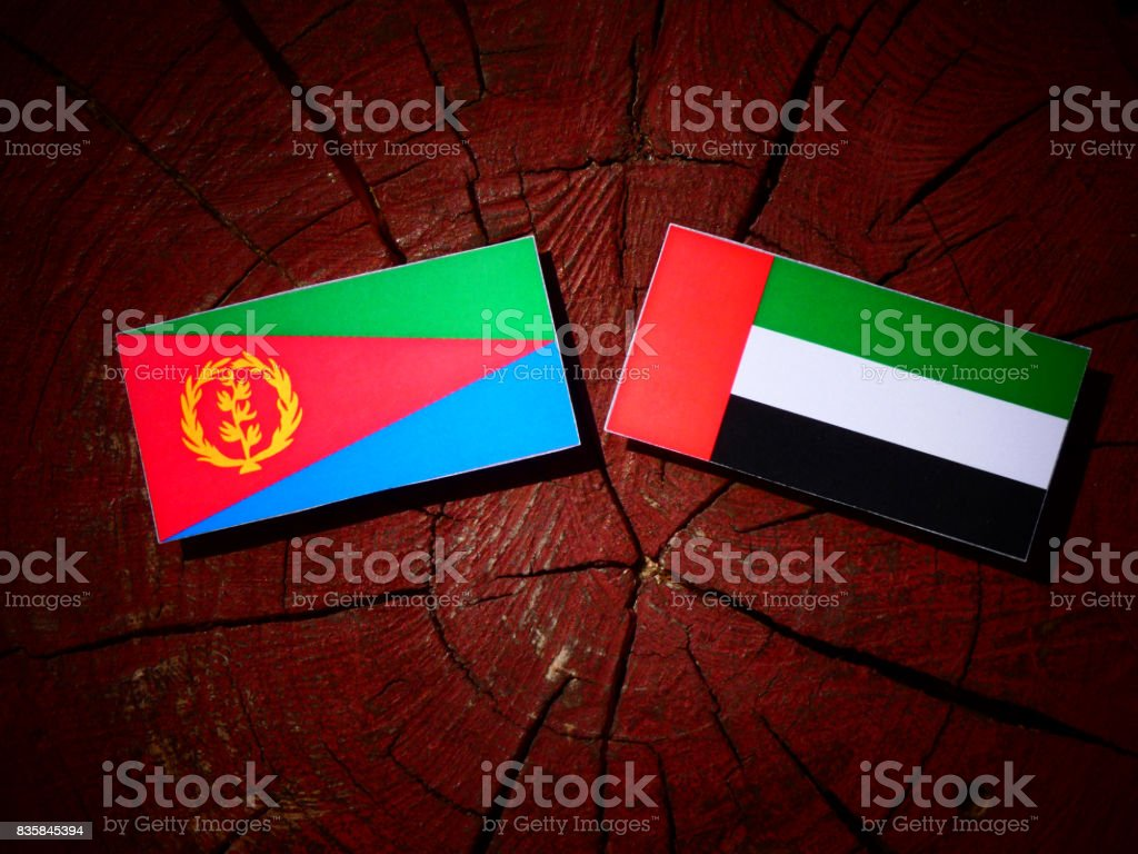 Eritrean flag with United Arab Emirates flag on a tree stump isolated stock photo