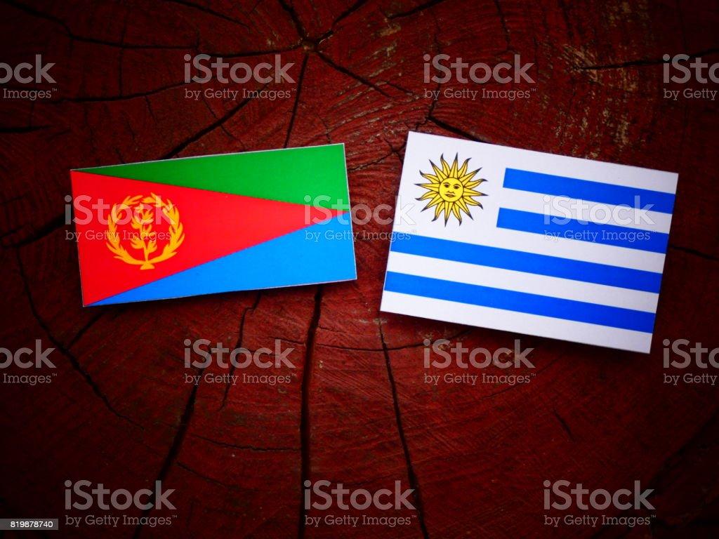 Eritrean flag with Uruguaian flag on a tree stump isolated stock photo