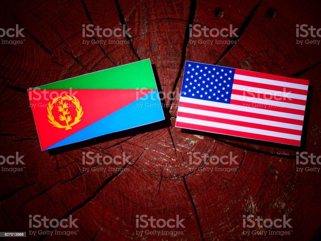Eritrean flag with USA flag on a tree stump isolated stock photo