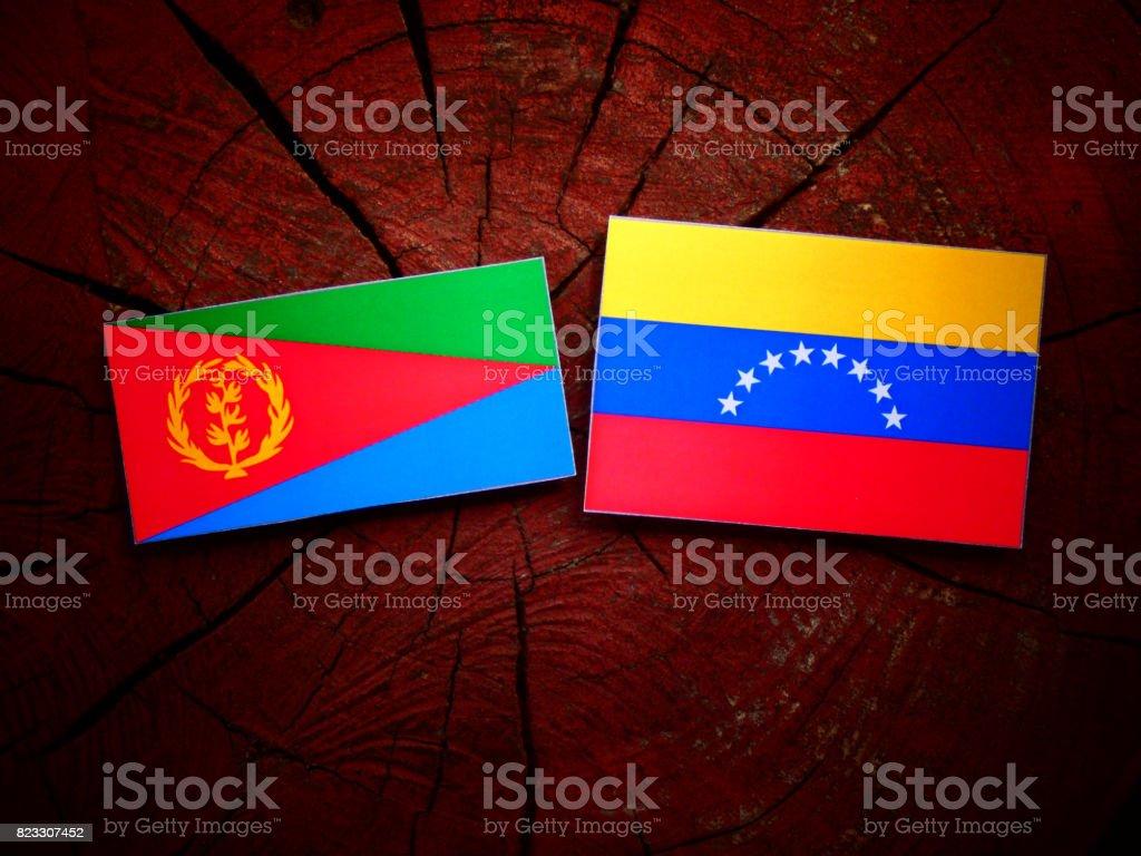 Eritrean flag with Venezuelan flag on a tree stump isolated stock photo