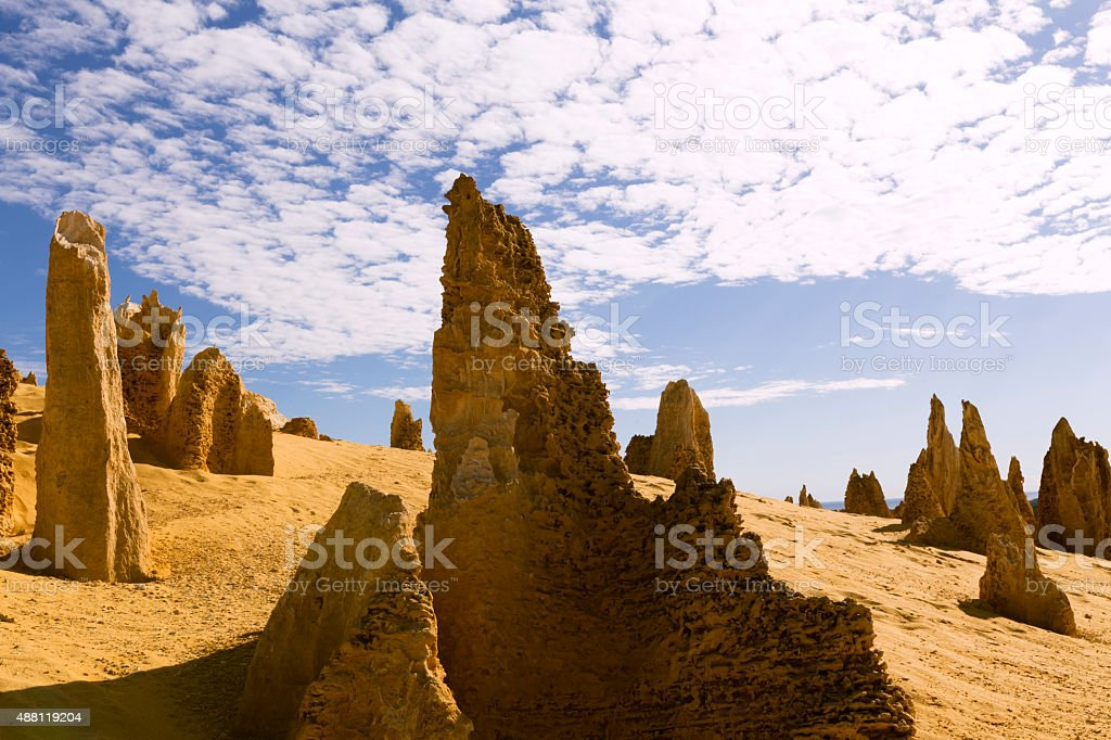 Eroded Pinnacles Mounted on a Sand dune under Fluffy Clouds stock photo