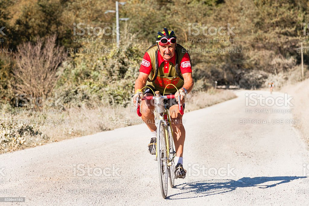 L'Eroica - Cyclist climbing a dirty white road in Tuscany stock photo