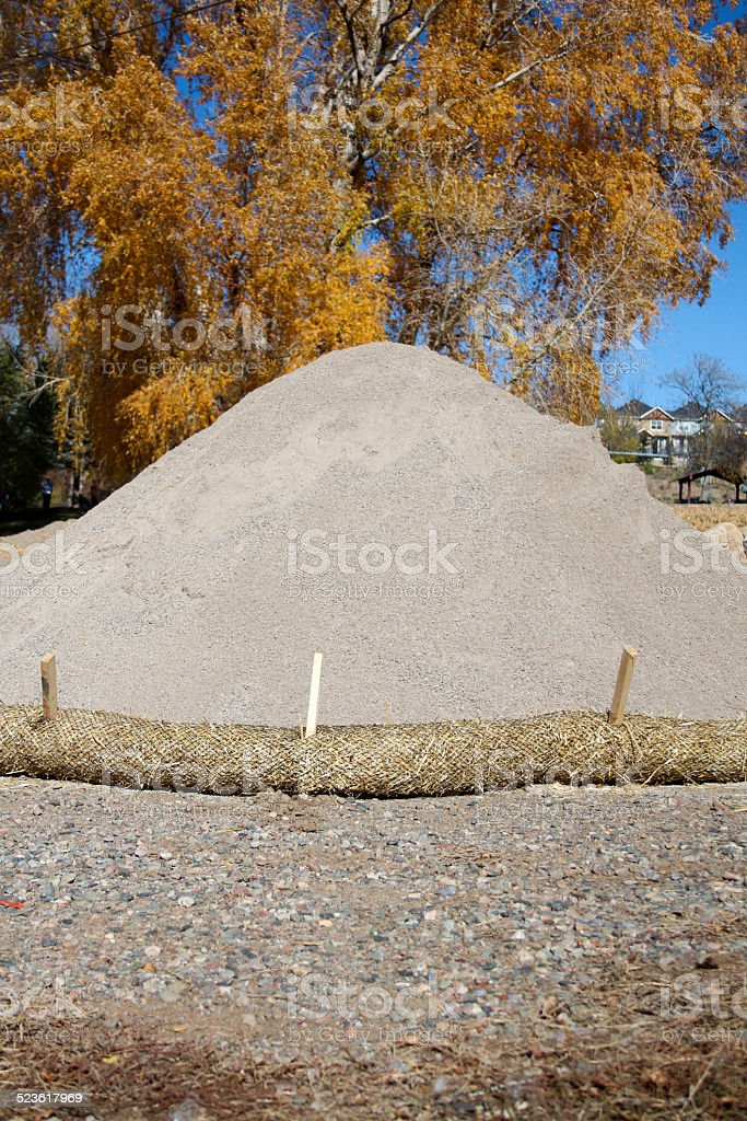 Erosion control, pile of sand, and yellow fall leaves stock photo