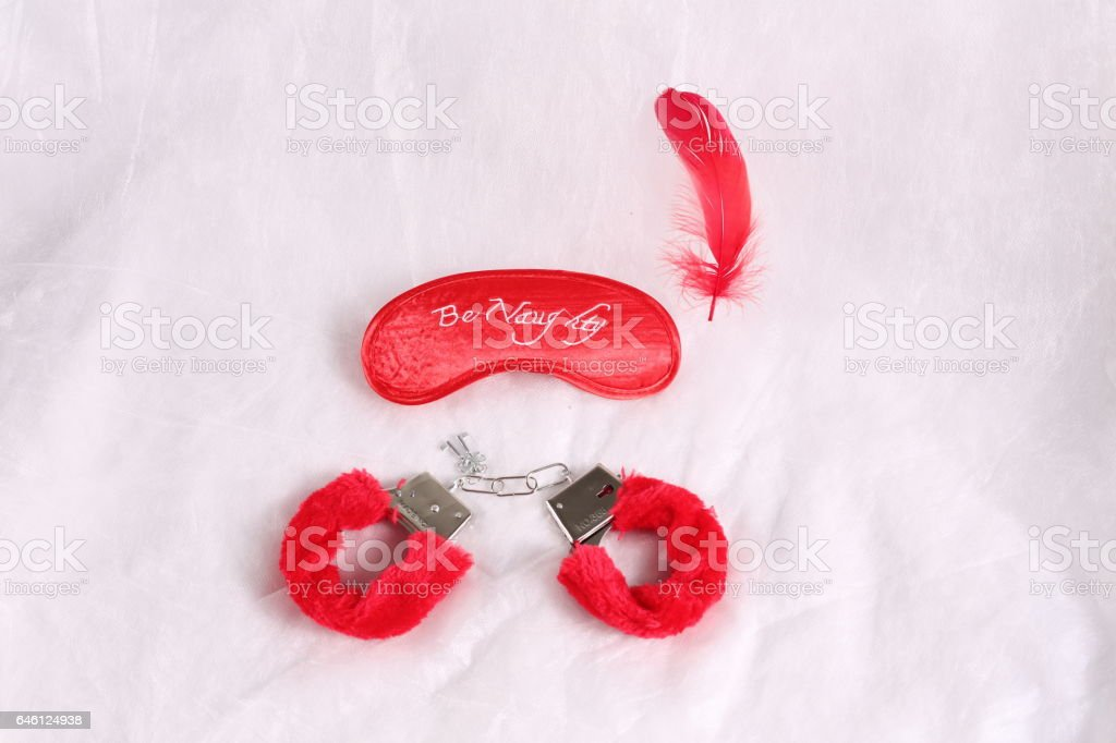 Erotic sexual face pack and handcuffs with fur on a white background stock photo