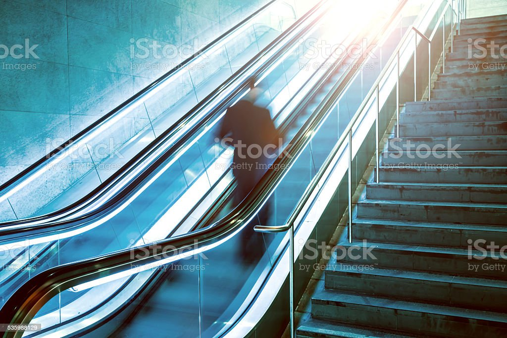 Escalator with business man stock photo