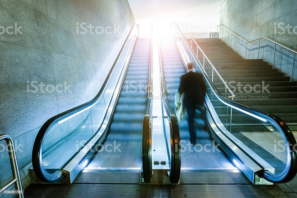 Escalator with businessman stock photo