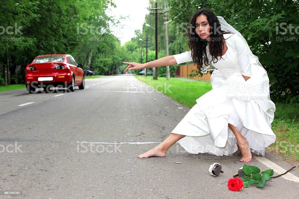 escape beautiful bride - hitch-hike at the road stock photo