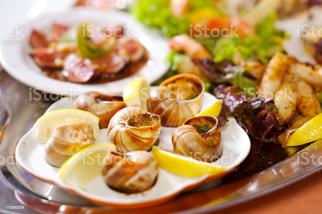 Escargot presented in ceramic, with butter and lemon royalty-free stock photo