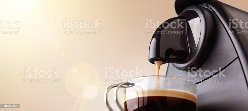 Espresso machine making coffee with beige gradient background stock photo