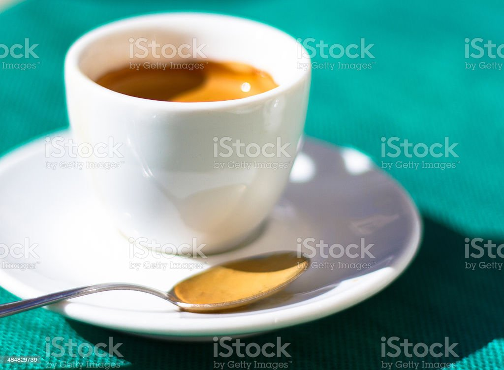Espresso with Spoon in White Cup and Saucer; Green Background stock photo