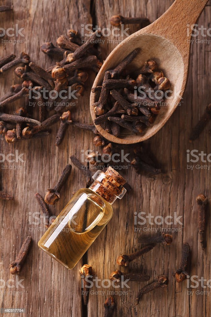 essence of cloves in the bottle macro  vertical top view stock photo