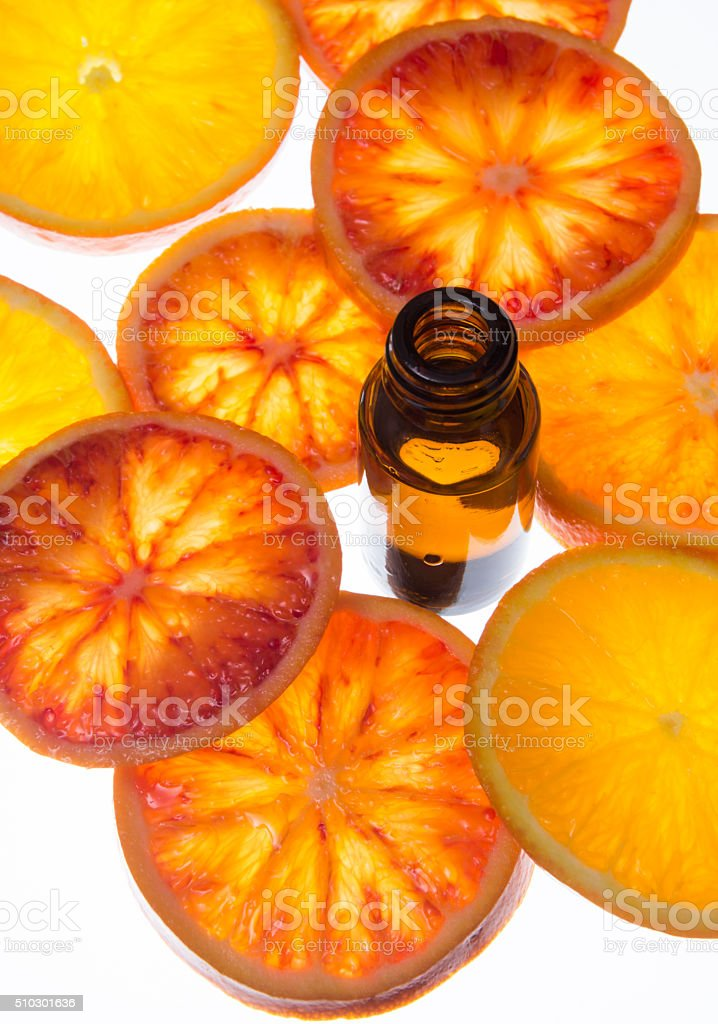 Essential oil bottle with blood orange slices with backlight stock photo
