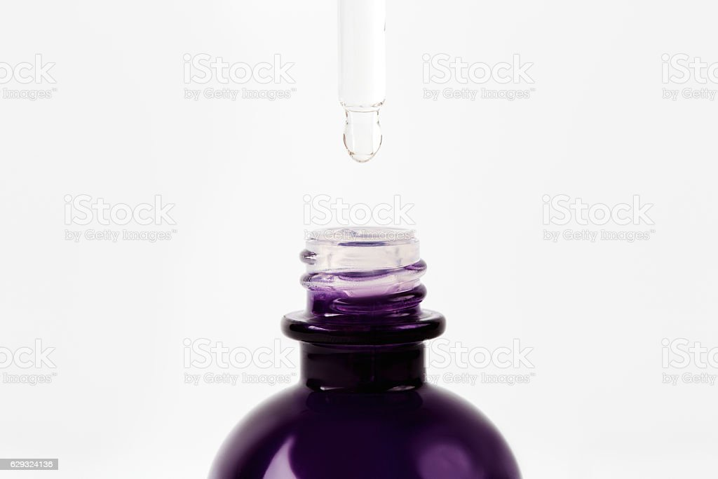 Essential oil or serum dropping from pipette to the bottle stock photo