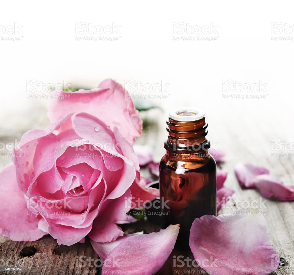 Essential oil with roses on a wooden table stock photo