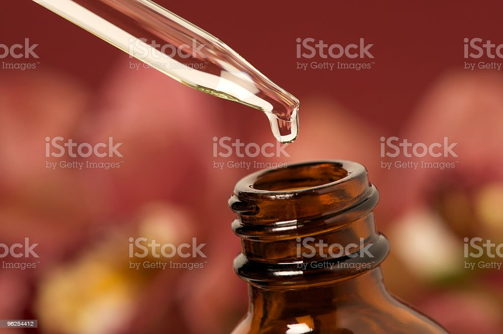 Essential oils with dropper above bottle stock photo