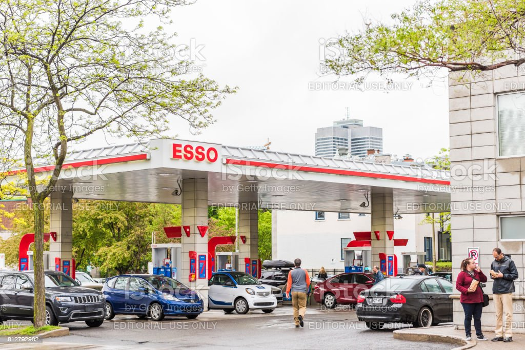 Esso gas station in downtown for car fuel with prices and people stock photo