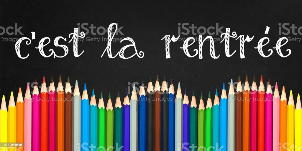 C'est la rentree (meaning Back to schoo in french) written on a black board background with a wave of colorful wooden pencils stock photo