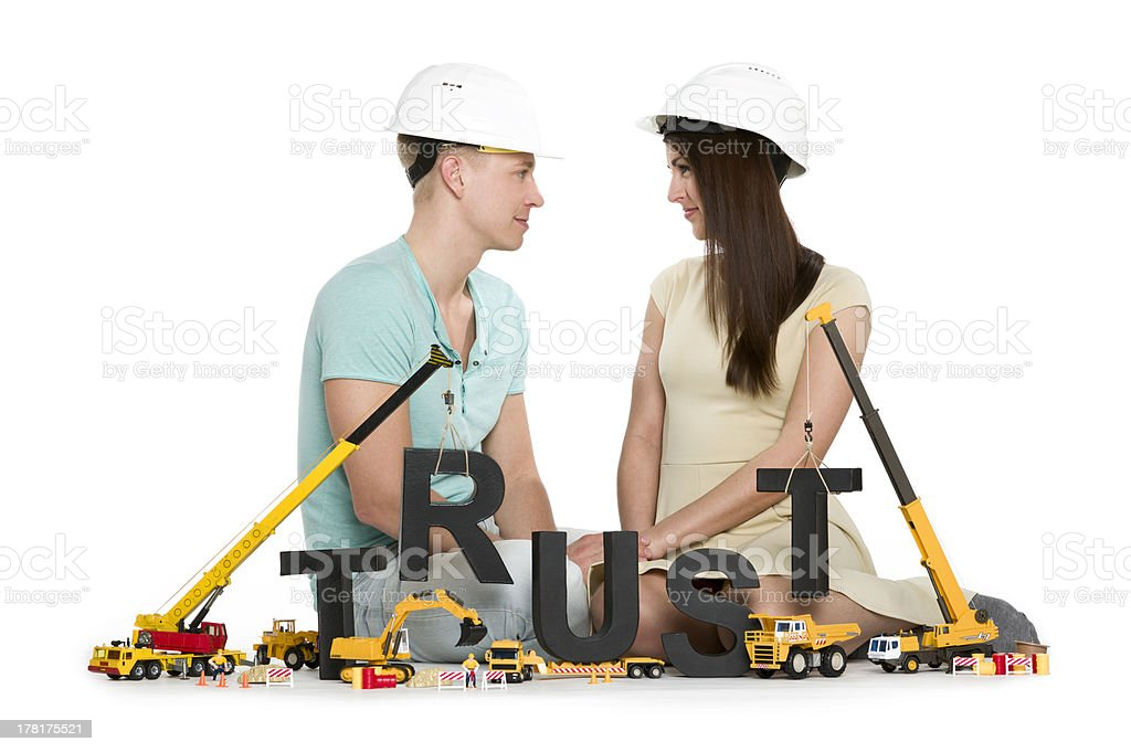 Establishing trust: Young couple with machines building trust-word. royalty-free stock photo