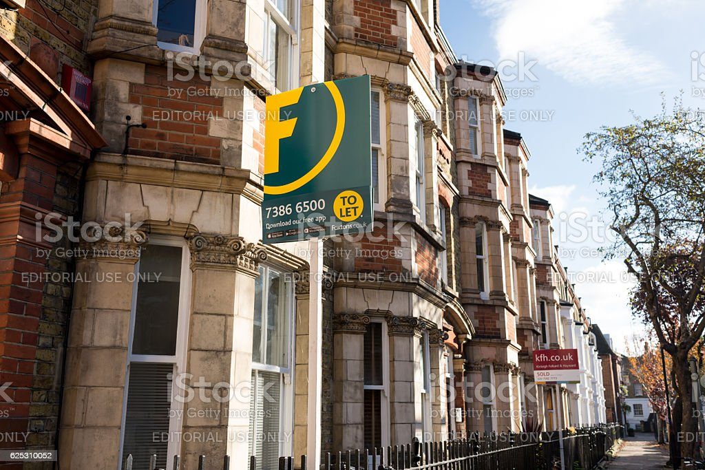 Estate agent signs outside Victorian terraced houses stock photo