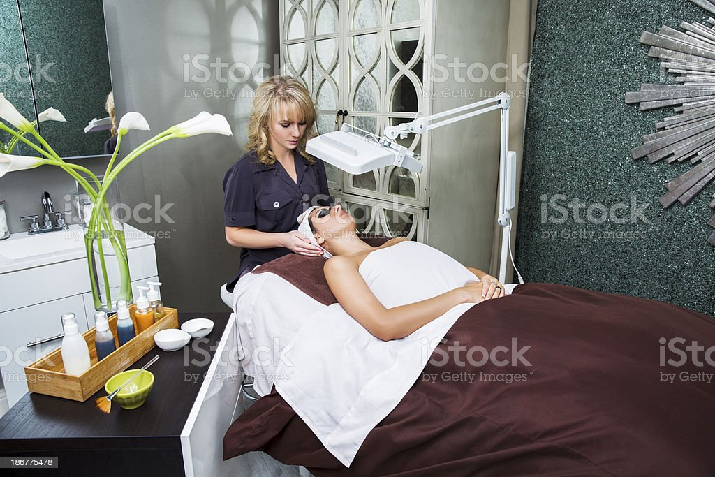 Esthetician performing light therapy facial treatment at the medical spa stock photo