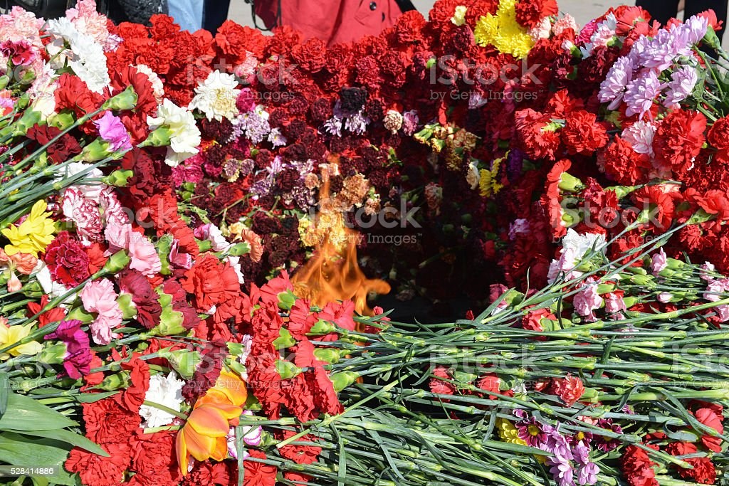 Eternal flame full of flowers stock photo