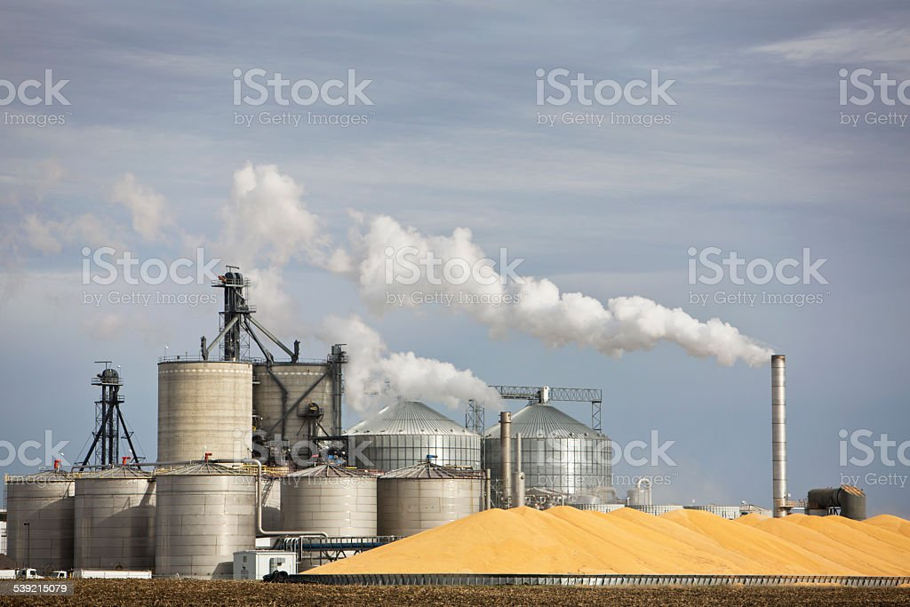 Ethanol Plant and Large Pile of Corn in The Midwest. stock photo