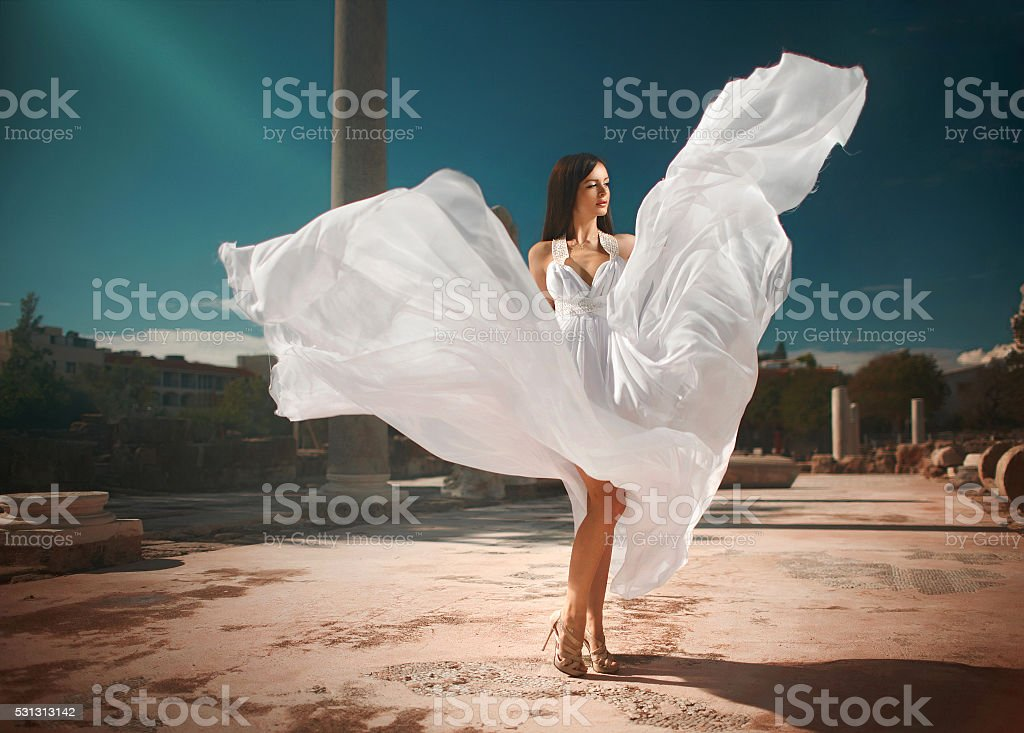 Ethereal, divine woman, girl with shiny dress standing in temple. stock photo