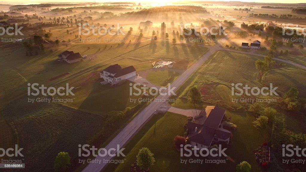 Etherial sunrise through misty fog with long shadows and sunbeams stock photo